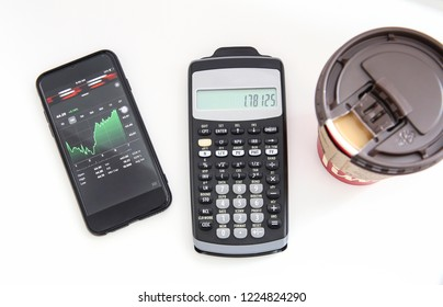 Winnipeg, Manitoba / Canada - November 8, 2018:  Minimalist  office desk with a stock watchlist, a calculator, and a cup of coffee. Canadian Investor Tools.