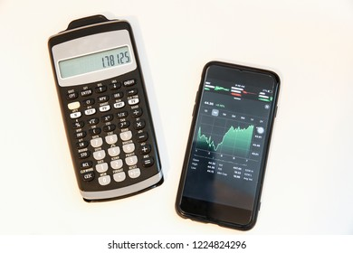 Winnipeg, Manitoba / Canada - November 8, 2018:  Minimalist office desk with a stock watchlist and a calculator. Investor Tools.