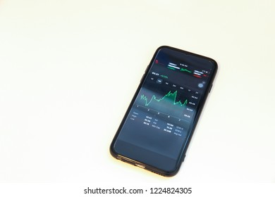 Winnipeg, Manitoba / Canada - November 8, 2018:  Minimalist office desk with a stock watchlist on the smartphone. Investor Tool.