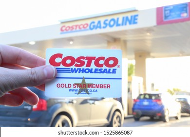 Winnipeg, Manitoba / Canada - October 7, 2019: Costco Card Membership in the First Plan with Cars Line at Gas Station in the Background.