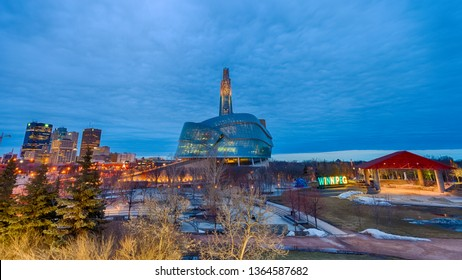 Winnipeg, Manitoba/Canada - April 2019: The Canadian Museum for Human Rights, a distant view of downtown buildings, the illuminated Winnipeg sign, all viewed from the Forks in the evening