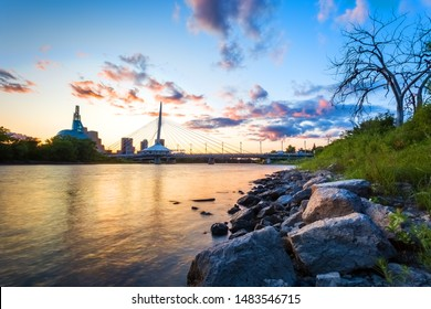 Winnipeg, Manitoba/Canada - August 2019: The Canadian Museum for Human Rights and the Esplanade Riel pedestrian bridge viewed at sunset, with the Red River as the foreground