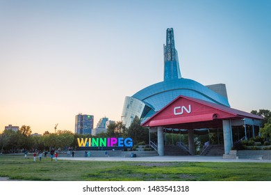 Winnipeg, Manitoba/Canada - August 2019: The CN Stage at the Forks and the illuminated Winnipeg sign near sunset, with the Canadian Museum for Human Rights looming in the back