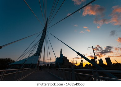 Winnipeg, Manitoba/Canada - August 2019: Silhouettes of the Esplanade Riel pedestrian bridge, the Canadian Museum for Human Rights in the back, as well as various buildings near sunset