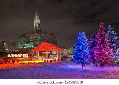 Winnipeg, Manitoba/Canada - December 2018: People skating outdoors at the Forks National Historic Site, with Christmas trees lit up and the Canadian Museum for Human Rights in the background