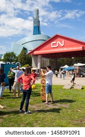 Winnipeg, Manitoba/Canada - July 2019: A couple plays a giant-sized game of Jenga at the Forks. The Canadian Museum for Human Rights can be seen in the background