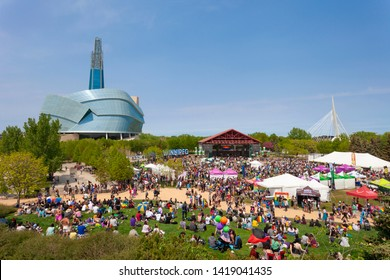 Winnipeg, Manitoba/Canada - June 2019: A large assembly of people is gathered at the Forks to celebrate Pride Weekend 2019 in Winnipeg. The Canadian Museum for Human Rights can be seen in the back