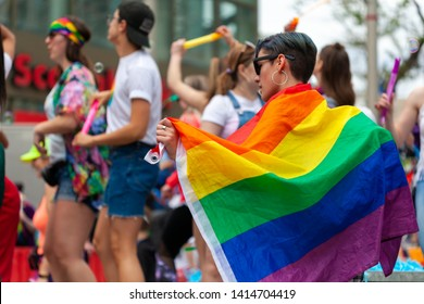 Winnipeg, Manitoba/Canada - June 2019: A Pride parade attendee marches with a Pride flag draped over their shoulder, with other attendees visible in the background