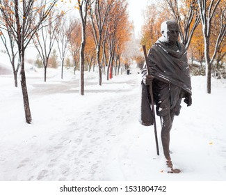 Winnipeg, Manitoba/Canada - October 2019: The Mahatma Gandhi statue and some trees are partially covered in snow after a snow storm in autumn