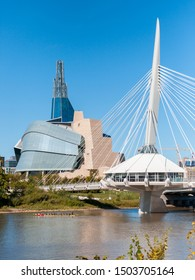Winnipeg, Manitoba/Canada - September 2019: A group of people rowing on a dragon boat on the Red River, with the Canadian Museum for Human Rights and the Esplanade Riel footbridge in the background