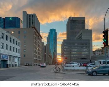 Winnipeg, MB/CAN - 07-26-2019:  Sun going down on urban streetscape in downtown Winnipeg