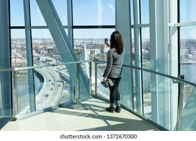 Winnipeg, MB/Canada - April 2019: A woman takes a photo of the Provencher bridge and the Esplanade Riel footbridge from the Israel Asper Tower of Hope inside the Canadian Museum for Human Rights