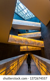 Winnipeg, MB/Canada - April 2019: A woman walking through an illuminated corridor inside the Canadian Museum for Human Rights, with more illuminated walkways overhead