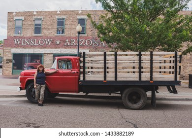 winslow Arizona, USA 5/16/2016.  Flatbed ford with woman. Side of building with art work windows, people hugging, eagle, truck with female driver. Signs, statue