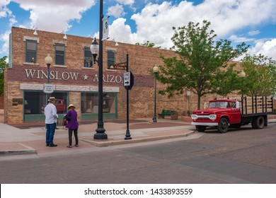 winslow Arizona, USA 5/16/2016. Two people standing on the corner. Side of building with art work windows, people hugging, eagle, truck flatbed ford