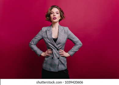 Winsome business lady with short haircut posing in studio. Photo of confident girl in tweed jacket isolated on claret background.