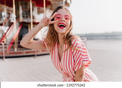 Winsome female model in vintage striped dress dancing in amusement park. Outdoor portrait of blissful blonde woman in sunglasses standing near carousel with peace sign.