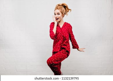 ad00de337c Winsome girl in red pajamas jumping and laughing in morning. Indoor photo  of blonde woman