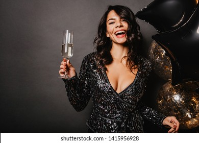 Winsome tanned girl raising wineglass. Indoor photo of charming latin lady isolated on dark background.