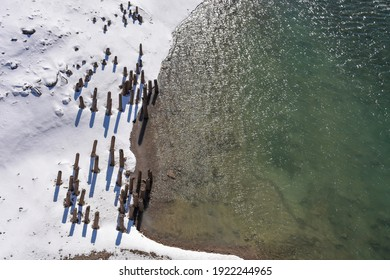 Winter abstract of overhead view of circular pattern of old dock pilings in snow.