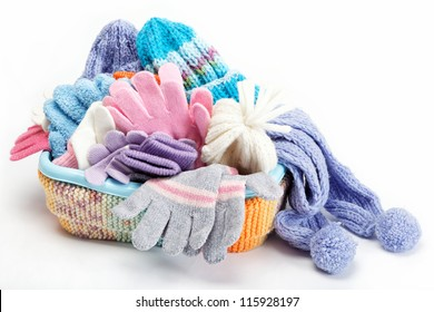 Winter accessory collection. Hat, scarf and mittens in the container, isolated on white background.