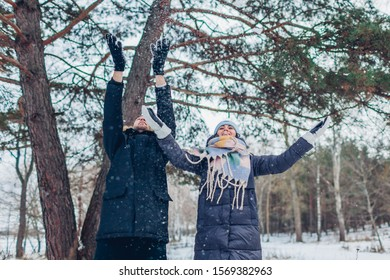 Winter activities. Couple throwing snow up in winter forest. People relaxing and having fun outdoors