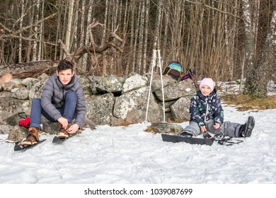 Winter activity. A boy and girl sitting in the snow putting on their skis against a stone wall.