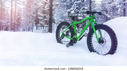 winter adventures - fat bike standing in the snow on snowy finland lapland forest background. copy space
