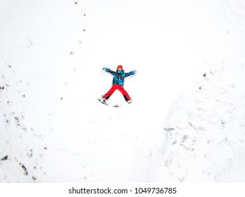 Winter aerial drone landcape with fun kid on snow