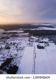 Winter aerial with small village and snowy landscape. Polish village under snow photographed from drone