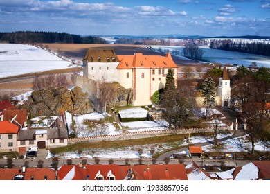 Winter, aerial view of Kamen castle over red roofs of village houses, illuminated by sun. Castle near to Prague built on granite rock against blue sky with white clouds. Travel point, Czech landscape. - Shutterstock ID 1933857056