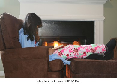 Winter Afternoon. Girl reading while curled up by the fire