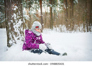 In the winter afternoon in a snowy forest, a girl sits in the snow under a pine tree.