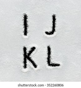 Winter alphabet, symbols and numbers hand written on snow. Black background isolated. Letters I, J, K, L.