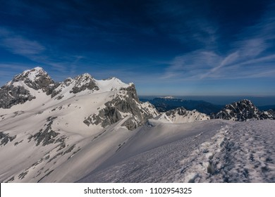 Winter alpine landscape with snow, high alpine peaks and summits. Mount Skuta and Rinka in Kamnik Savinja Alps, Slovenia. Blue sky and beautiful day in the mountains.