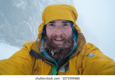 winter alpine misery, mountaineer taking a selfie in a bad weather in a winter mountains