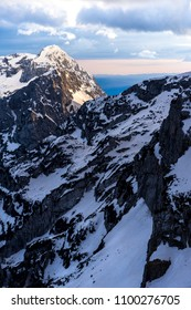 Winter alpine mountain landscape of Kamnik-Savinja Alps, Slovenia. Sunset or sunrise in high mountains with rocky peaks and summits. Kalska Gora near Kamnik. High alpine peak in sunset light.