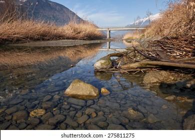 Winter Alpine River with a Bridge