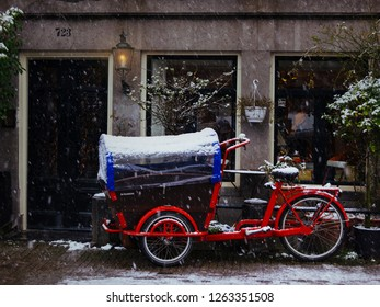 winter in amsterdam: red bakfiets covered with snow