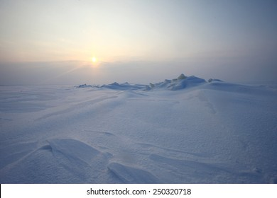 Winter antarctica landscape. Plain of snow, ice and low Northern sun