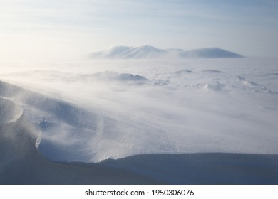 Winter Arctic landscape. View of the snow-covered tundra and snow-covered mountains. Very cold and windy weather. Blowing blizzard. Chukotka, Siberia, Russia. Low depth of field, blurred background.
