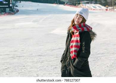 Winter Asian Woman Smiling in Snow. Beautiful Young Asian Woman Enjoying the Snow in Skii Resort dressed in a Black Coat, Cheerful Red Strip Winter Scarf and White Hat. Happy Winter Holiday.