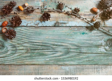 Winter ( autumn) border design on the wooden background. Brown pinecones and oak acorns on old wood background top view. Christmas pine cone border with place for text. High resolution.