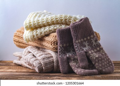 Winter, autumn clothes, knitted scarves and warm mittens on a white background.