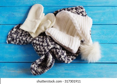 winter baby clothes, hat, scarf and mittens on a blue wooden background.