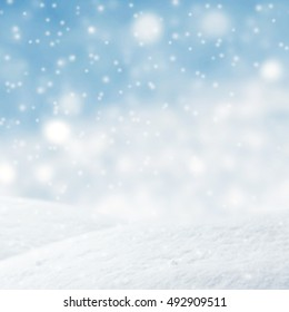 Winter background, Abstract blue lights Christmas background with falling snowflakes, copy space. For a greeting or message about promotions and sales.