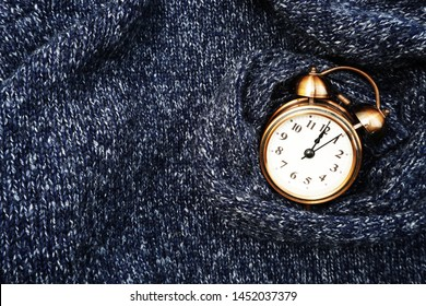 Winter background with alarm clock on blue knitted texture background