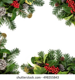 Winter background border with holly and red berries, ivy, snow covered pine cones and fir over white.