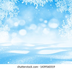 Winter background. Winter bright landscape with snowdrifts and falling snow. Branches of trees in hoarfrost.