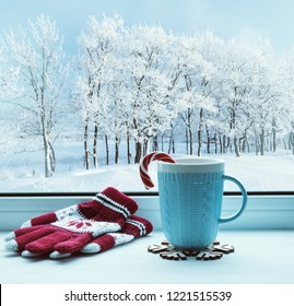 Winter background. Cup with candy cane on windowsill and winter trees outdoors. Winter festive composition